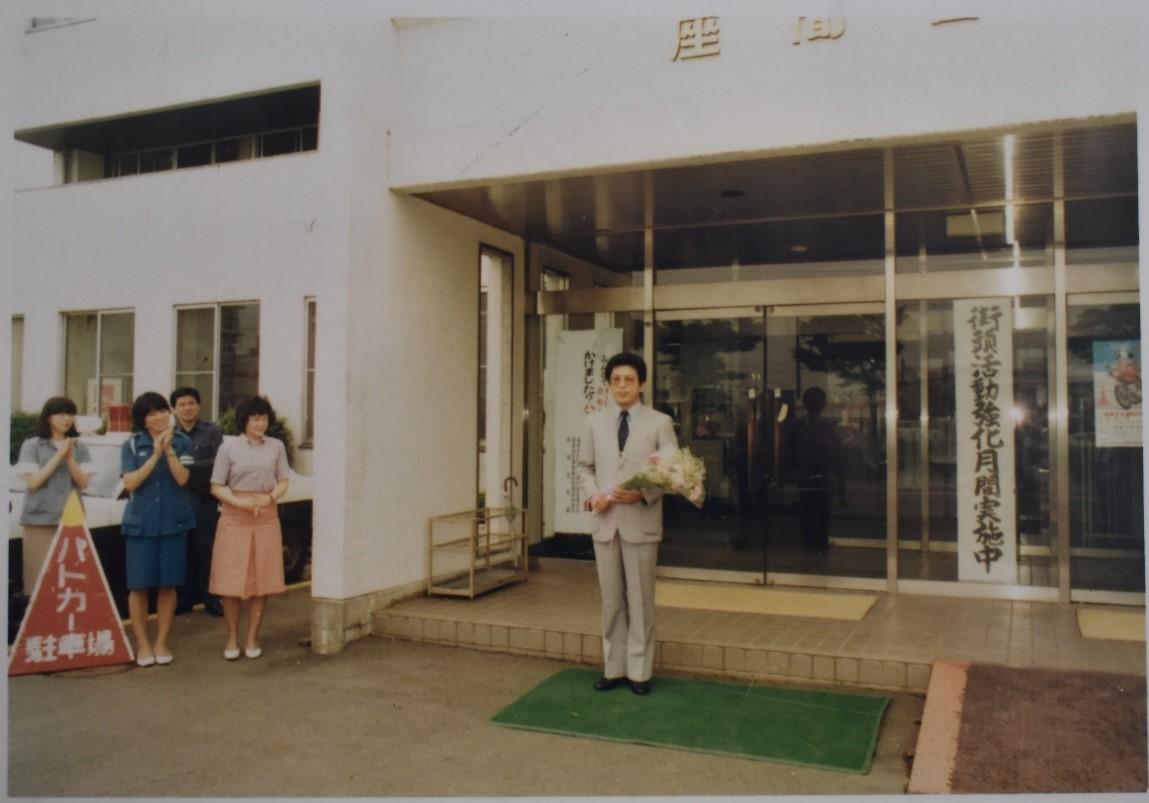 退職のとき贈られた花束を手にして女子職員らに見送られる八木会長